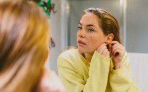 Женщина чистит ушной прокол