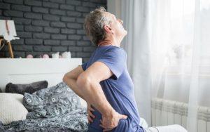 Мужчина наблюдает утреннюю боль в спине