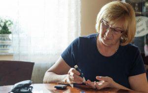 Женщина измеряет уровень сахара в крови
