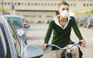 Женщина в маске едет на велосипеде