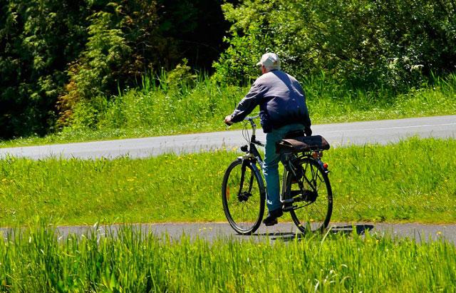 пожилой мужчина катается на велосипеде