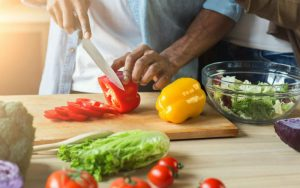 Мужчина режет овощи