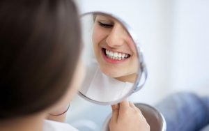 Женщина осматривет зубы в зеркале